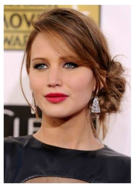 loose bun with long side swept bangs hairstyles for round faces